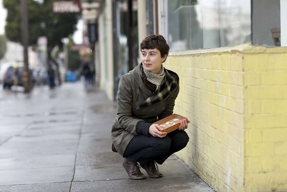 Julie Cloutier poses for a portrait on the corner of 16th and Guerrero Streets next to where she placed a portrait of a rock she collected there as part of an art project in San Francisco, Calif., on Monday, April 25, 2011.  Cloutier collected rocks she found on the street, painted portraits of them and then placed the portraits in the precise location where the original rock was found.  Her work is part of a group show at San Francisco Art Institute. Photo: Laura Morton, Special To The Chronicle