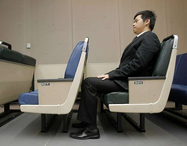 Tom Lee demonstrates the mobile seating lab's legroom comparison as potential new BART train seating arrangements are unveiled during a media preview at Joseph Bort Metrocenter in Oakland, Calif., on Sunday, April 24, 2011. Photo: Thomas Levinson, The Chronicle