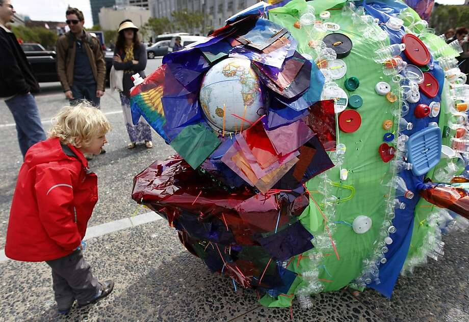 "Damian Stil, 4, vacationing with his parents from Amsterdam, peers into a fish sculpture made from plastic representing floating ocean trash at the Earth Day festival at Civic Center Plaza in San Francisco on Saturday. Students from the Quarry Lane School in Pleasanton created the ""School of Fish"" artwork in collaboration with artist Tim Crowe. Photo: Paul Chinn, The Chronicle"