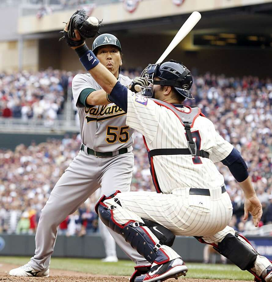 Minnesota Twins catcher Joe Mauer, right, barely snags the ball on a pitch against Oakland Athletics' Hideki Matsui (55) during the ninth inning of an MLB baseball game on Friday, April 8, 2011, in Minneapolis, Minn. The Twins defeated the Athletics 2-1. Photo: Genevieve Ross, AP