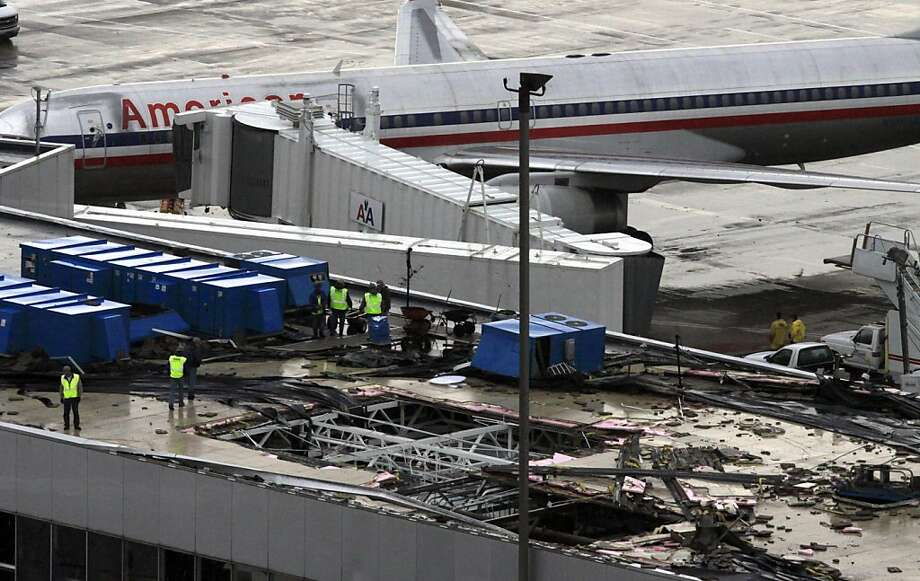 Crews inspect damage to the roof of Concourse C at Lambert-St. Louis International Airport Saturday, April 23, 2011, in St. Louis. Lambert Airport is expected to reopen Sunday, two days after a strong tornado caused significant damage at the St. Louis airport. St. Louis Mayor Francis Slay says the airport could be operating at 70 percent capacity starting Sunday but will reopen only if power is restored. An Ameren Missouri spokesman says power should be restored later Saturday. The airport director says one American Airlines 757 jet sustained significant damage, and four other American planes had minor damage. Five or six flights had to be diverted away from St. Louis when the storm hit. Photo: Jeff Roberson, AP