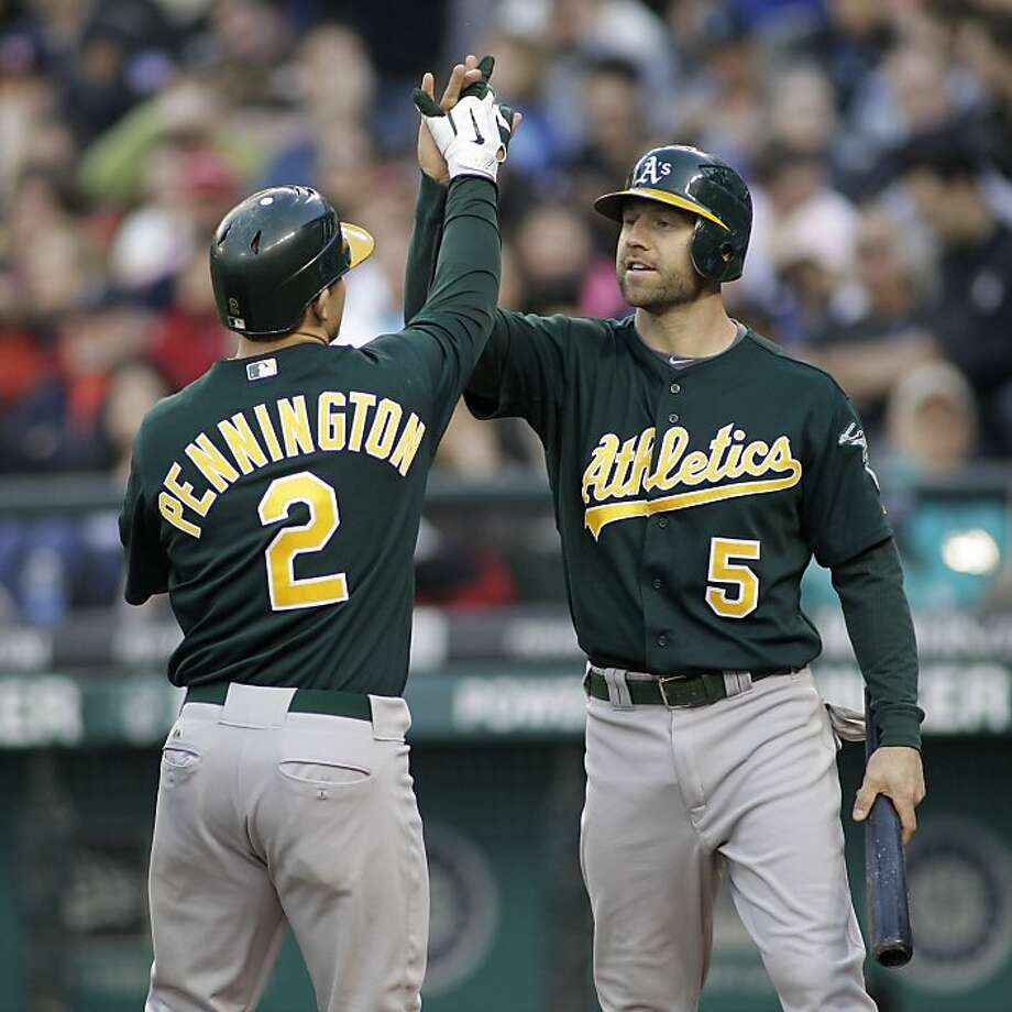 Oakland Athletics' Kevin Kouzmanoff (5) greets Cliff Pennington at the plate after Kouzmanoff scored on Pennington's two-run home run against the Seattle Mariners in the fourth inning of a baseball game, Saturday, April 23, 2011, in Seattle. Photo: Ted S. Warren, AP