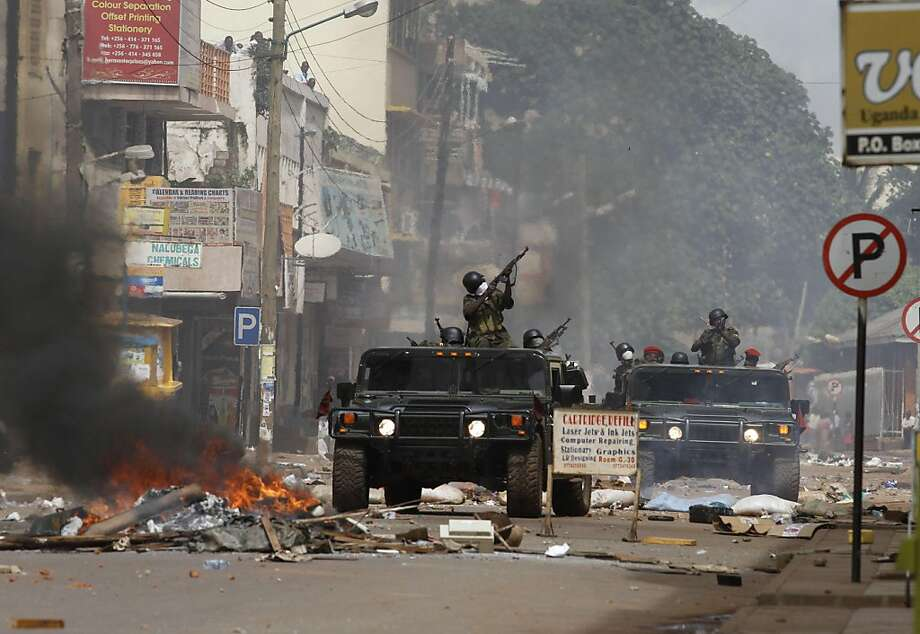 Ugandan soldiers shoot at demontrators, who pelt them with rocks from apartment buildings, during riots in Kampala on April 29, 2011, a day after Uganda's opposition leader Kizze Besigye was arrested for the fourth time this month. Rioters setting tyres alight in Kampala clashed with police firing tear gas, leaving one dead and dozens in hospital. On April 28, opposition leader Kizza Besigye was arrested by police who smashed his car windows with guns and hammers before bundling him into the back of pick-up truck. Besigye and other opposition leaders earlier in April started walking to work twice a week as a symbolic protest against rising fuel costs but the demonstrations have met with a tough response from the police. Photo: Marc Hofer, AFP/Getty Images