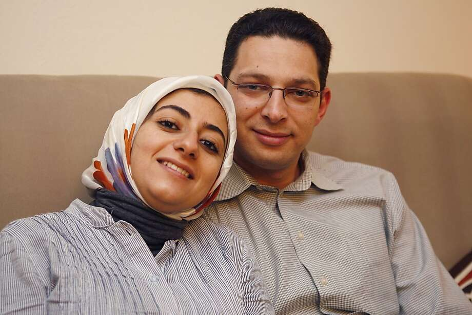 Yasmeen Daifallah and Mohamed Talaat sit together on the couch in their Oakland Calif, apartment on Wednesday, April 13, 2011. The couple met when Yasmeen was a college student in Cairo and Mohamed was visiting his home town while enrolled as a doctoral student at UC Berkeley. Photo: Alex Washburn, The Chronicle