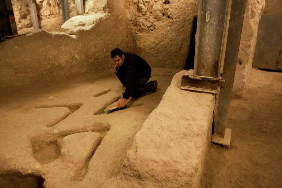 ASSOCIATED PRESS NO THEORY: Israel's Antiquities Authority archaeologist Eli Shukron sweeps marks carved in the bedrock in an archeological excavation in the City of David. The mysterious carvings made thousands of years ago were recently uncovered. Photo: Sebastian Scheiner / AP