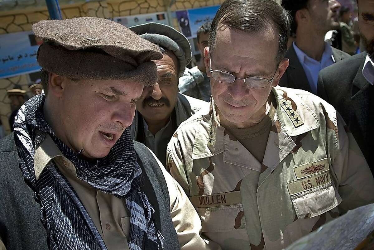 """FILE - In this July 15, 2009 file photo released by Department of Defense, """"Three Cups of Tea"""" co-author Greg Mortenson shows the locations of future village schools to U.S. Navy Adm. Mike Mullen, chairman of the Joint Chiefs of Staff, at the openingof Pushghar Village Girls School 60 miles north of Kabul in Panjshir Valley, Afghanistan. Montana's attorney general on Tuesday, April 19, 2011 told The Associated Press that he has launched an inquiry into the charity run by Mortenson, following investigations by """"60 Minutes"""" and author Jon Krakauer into inaccuracies in the book."""