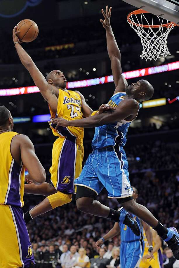 Los Angeles Lakers guard Kobe Bryant, left, goes up for a dunk as New Orleans Hornets center Emeka Okafor defends during the first half in Game 5 of a first-round NBA basketball playoff series, Tuesday, April 26, 2011, in Los Angeles. Photo: Mark J. Terrill, AP