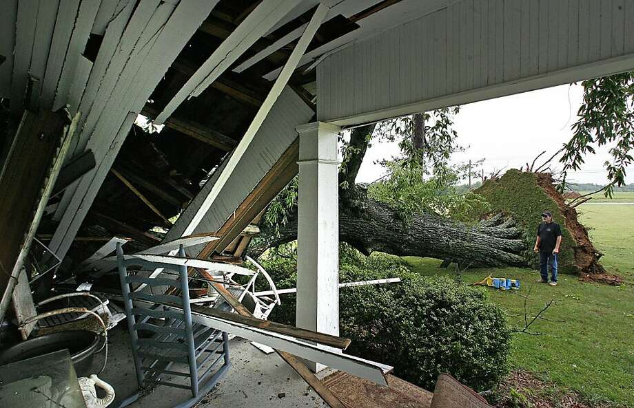 Karl Rhodes looks at the damage to a house in Florence, Ala., after storms caused a large tree to fall  on Tuesday, April 26, 2011. The tree crushed a corner bedroom at Beth Scott's home where Rhodes does the grounds-keeping. Photo: Jim Hannon, AP