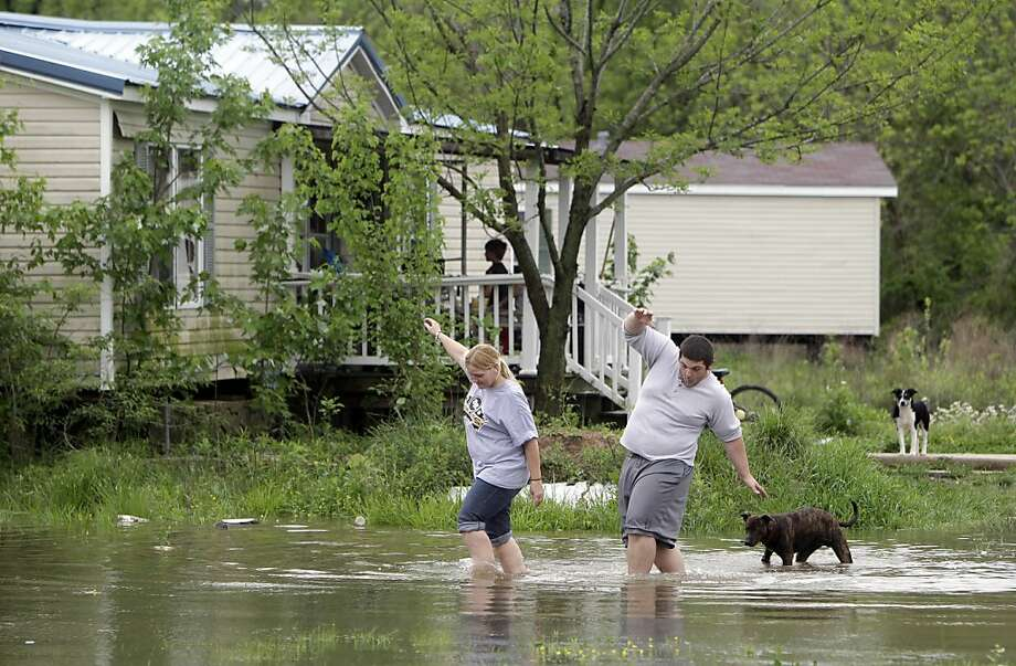 Eve Andrews, left, and her son Brandon Andrews walk through floodwater to get back to their home Monday, April 25, 2011, in Poplar Bluff, Mo. Thousands of southeastern Missouri residents watched helplessly Monday as water from the Black River crept towardtheir homes after flowing over the levee protecting their town and trapping some who had to be rescued by boat. Photo: Jeff Roberson, AP
