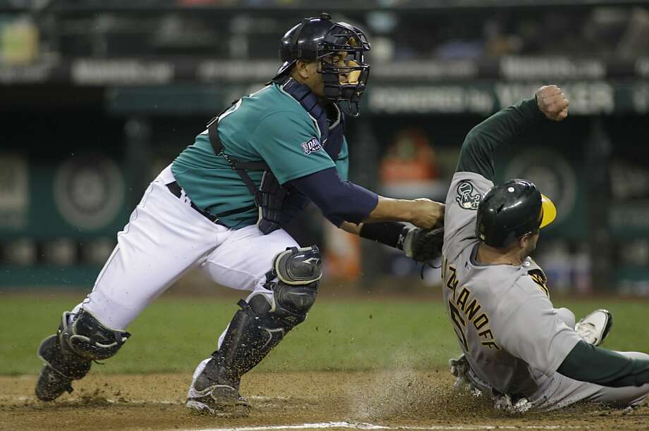 Seattle Mariners catcher Miguel Olivo tags out Oakland Athletics' Kevin Kouzmanoff at the plate in the fifth inning of a baseball game, Friday, April 22, 2011, in Seattle. Photo: Ted S. Warren, AP
