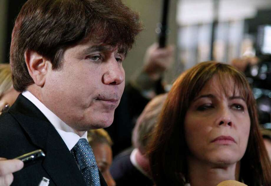 Former Illinois Gov. Rod Blagojevich, left, speaks to reporters as his wife Patti, right, listens at the federal building in Chicago, Wednesday, Dec. 7, 2011, after being sentenced for 14 years on 18 corruption counts, including trying to auction off President Barack Obama's old Senate seat. (AP Photo/M. Spencer Green) Photo: M. Spencer Green / AP