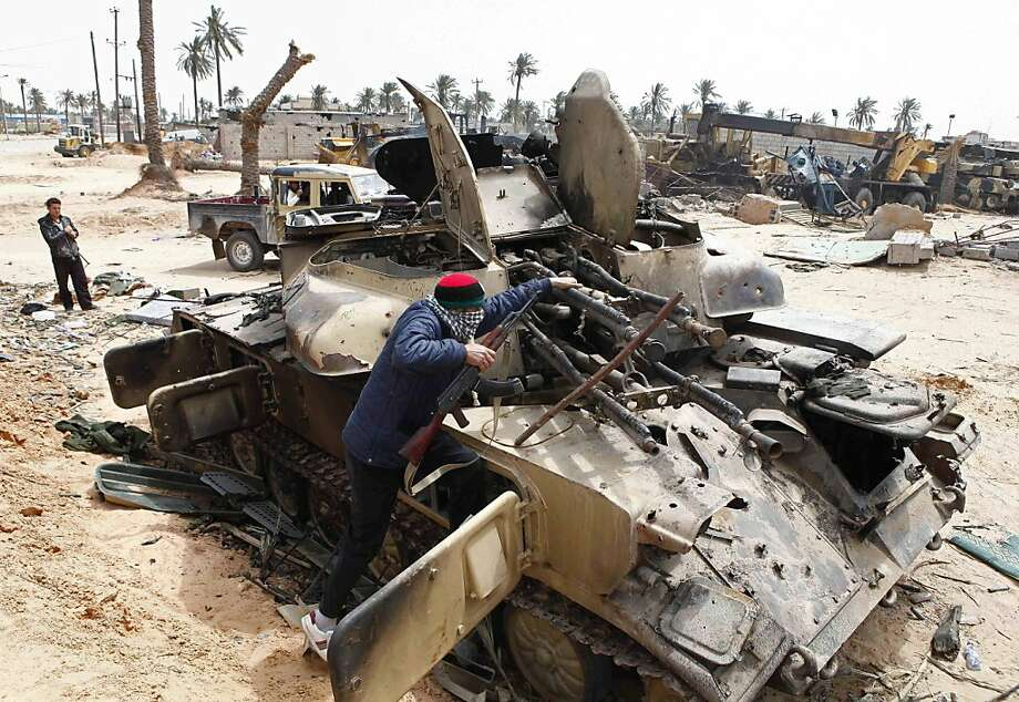 A Libyan rebel fighter climbs on  a destroyed government armored vehicle in the besieged city of Misrata, the main rebel holdout in Gadhafi's territory, Friday, April 22, 2011. Photo: Str, AP