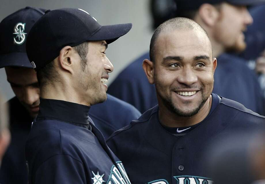 Seattle Mariners' Miguel Olivo, right, smiles with Ichiro Suzuki, left, after hitting a solo home run against the Detroit Tigers in the second inning of a baseball game in Detroit, Tuesday, April 26, 2011. The Mariners won 7-3. Photo: Paul Sancya, AP
