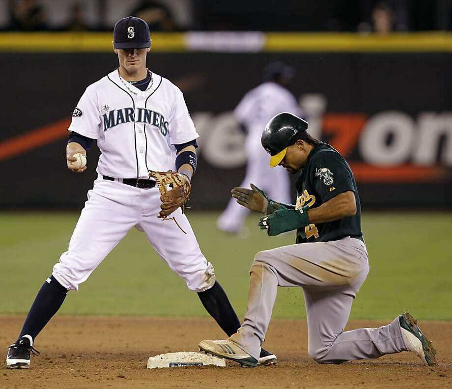 Seattle Mariners shortstop Brendan Ryan, left, looks at the ball as Oakland Athletics' Coco Crisp claps after stealing second base in the ninth inning of a baseball game Sunday, April 24, 2011, in Seattle. The Athletics won 5-2. Photo: Elaine Thompson, AP