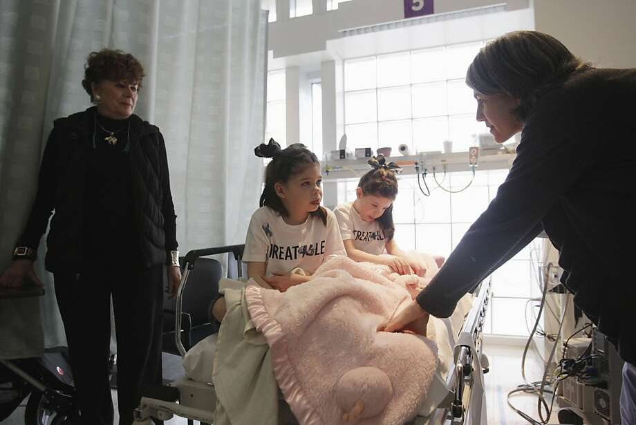 Chris Hempel, at right, comforts her twin daughters Cassidy, 6, center left, and Addison as their grandmother Helen Hempel, at left, looks on at the Children's Hospital and Research Center in Oakland, Calif., Friday, March 18, 2011. The Hempel twins are receiving alternative treatment for Niemann Pick Type C disease, a rare disorder where harmful amounts of cholesterol accumulates in vital organs.  Every other week, 7-year-old twins Addison and Cassidy Hempel have an experimental medicine injected into their spines in hopes of battling a fatal neurologic disease. It's not a drug company study _ their mother won a government OK for the unusual experiment. Photo: Marcio Jose Sanchez, AP