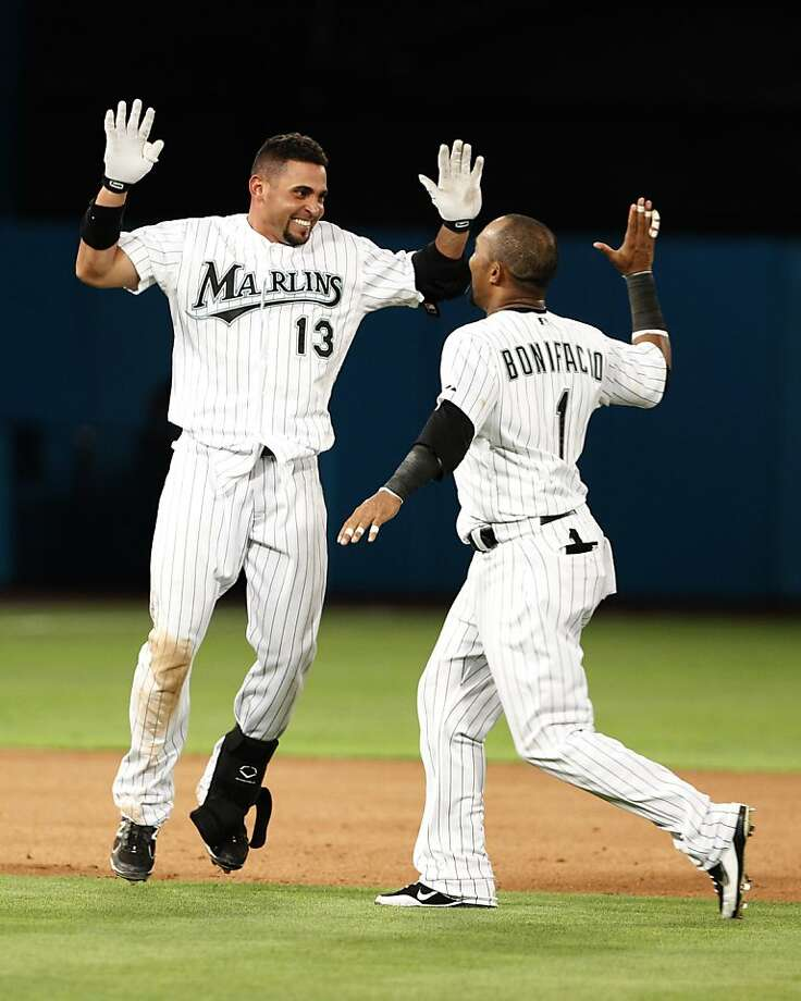 Florida Marlins' Omar Infante (13) celebrates with Emilio Bonifacio (1) after Infante hit a single to score Hanley Ramirez during the ninth inning of a baseball game as the Marlins defeated the Los Angeles Dodgers 5-4, Monday, April 25, 2011 in Miami. Photo: Wilfredo Lee, AP