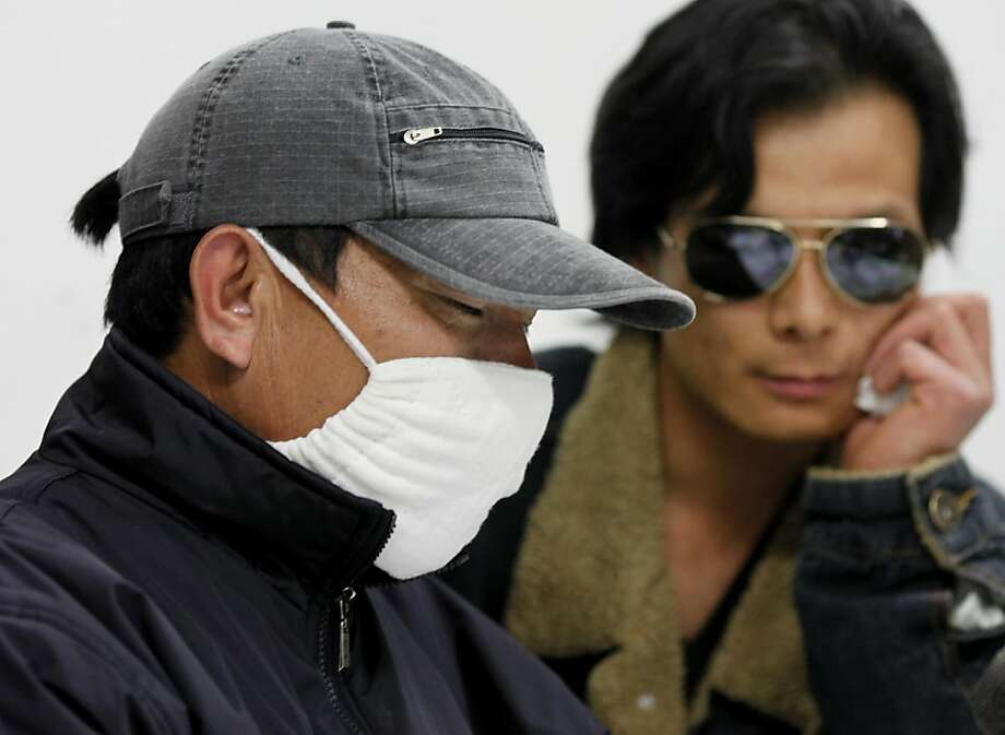The father of Andy Zeng, Zhi Xiang Zeng, (left) wore a mask because of a cold and because he did not want to draw attention to himself in the community.  He was joined by family friend Wei Jun Chen (right). A drive for relief assistance for the traumatized parents of shooting victim Andy Zeng in San Francisco, Calif. was announced at the Asian Pacific American Community Center Thursday April 21, 2011. Photo: Brant Ward, The Chronicle