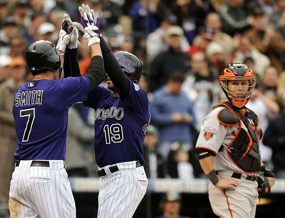 Colorado Rockies Seth Smith, left, congratulates Ryan Spilborghs, center, as San Francisco Giants catcher Buster Posey, right, watches after Spilborghs hit a three-run home run in the seventh inning of a baseball game at Coors Field in Denver on Wednesday, April 20, 2011. The Rockies won 10-2. Photo: Chris Schneider, AP