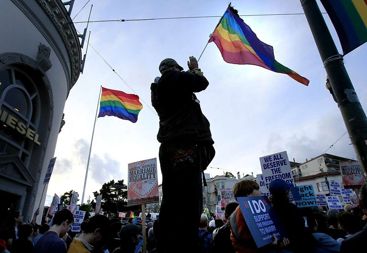 Maceo Garza stood with his flag and applauded a speaker at the corner of Market and Castro Streets in San Francisco on Wednesday, March 4, 2009.