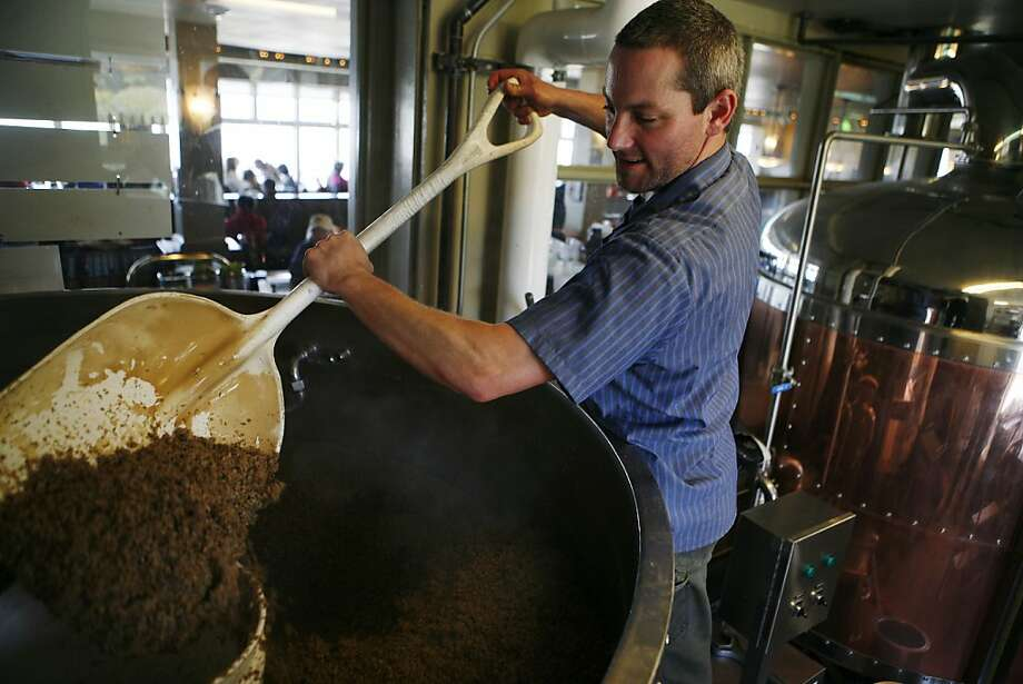 Brewer Aron Deorsey scoops out the used grain to be made into veggie burgers on Friday, April 15, 2011. At Beach Chalet, which brews its own beer, grain left over from the beer-making process, which still has plenty of nutritional value, goes into veggie burgers. Photo: Anna Vignet, The Chronicle