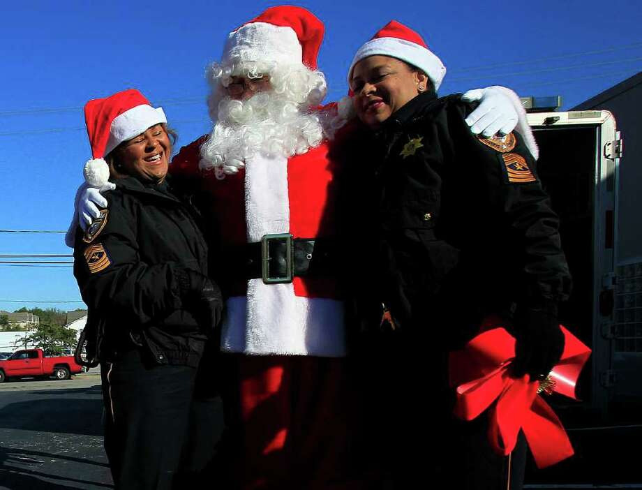 Harris County Sgt. Karen Jacobs, left, and Sgt. Jacqueline Fortune, right, share a laugh with Santa Claus in a parking lot near The Children's Assessment Center. Photo: Johnny Hanson, Houston Chronicle / © 2011 Houston Chronicle