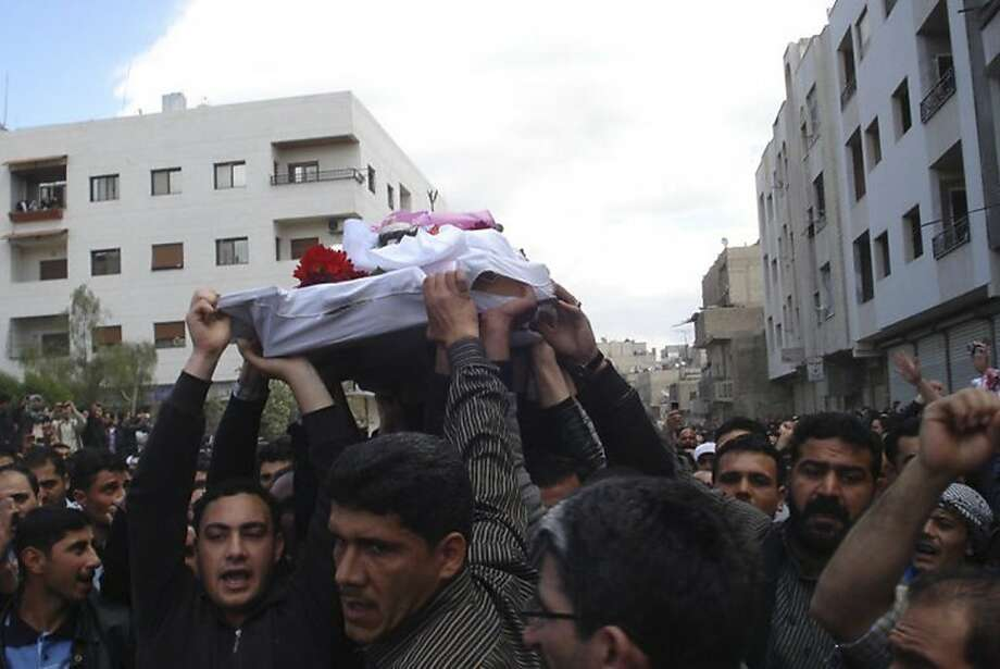 In this citizen journalism image made on a mobile phone and acquired Saturday April 23, 2011, by The AP, Syrian anti-government protesters carry the coffin of an activist who was killed on Friday during his funeral procession in Quaboun near Damascus, Syria, Saturday, April 23, 2011.  Syrian security forces fired on tens of thousands of mourners during funeral processions Saturday, killing several people following the deadliest day of the uprising against authoritarian President Bashar Assad. Photo: Associated Press