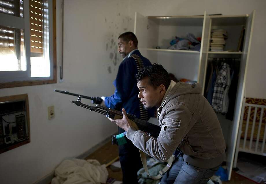 Two rebel fighters peak out a window in a trashed house on Tripoli street in the besieged city of Misrata on April 20, 2011. A group of rebel soldiers made their way from house to house along the frontline trying to target pro-loyalist snipers in surrounding buildings. Photo: Odd Andersen, AFP/Getty Images