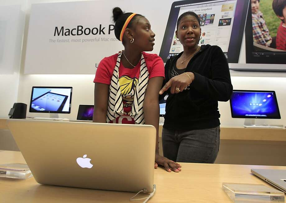 Apple customers Booke Carter, 13, and her mother Darnella Carter, right, talk about purchasing the Apple MacBook Pro at an Apple store in Palo Alto, Calif., Tuesday, April 19, 2011. Apple Inc. reports quarterly financial earnings Wednesday, April 20, after the market close. Photo: Paul Sakuma, AP