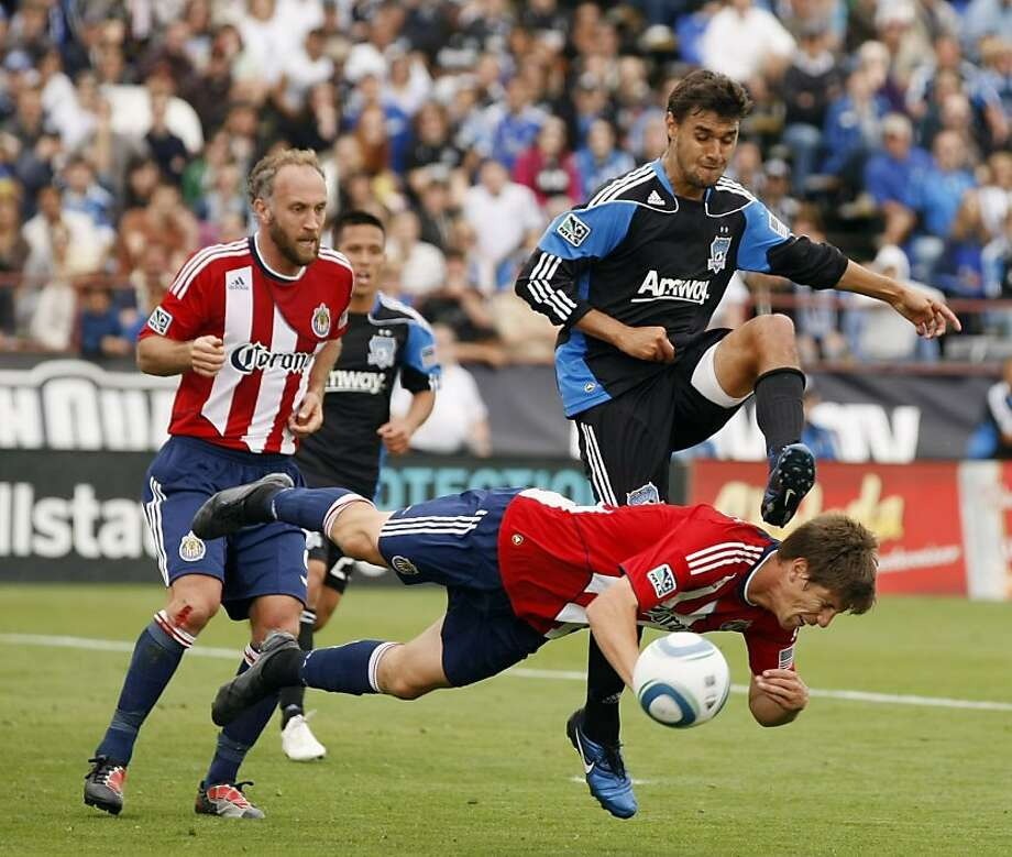 Chivas USA defender Andrew Boyens, bottom, battles against San Jose Earthquakes forward Chris Wondolowski, top right, during the second half of an MLS soccer game in Santa Clara, Saturday, April 23, 2011. Chivas USA won 2-1. Photo: Marcio Jose Sanchez, AP