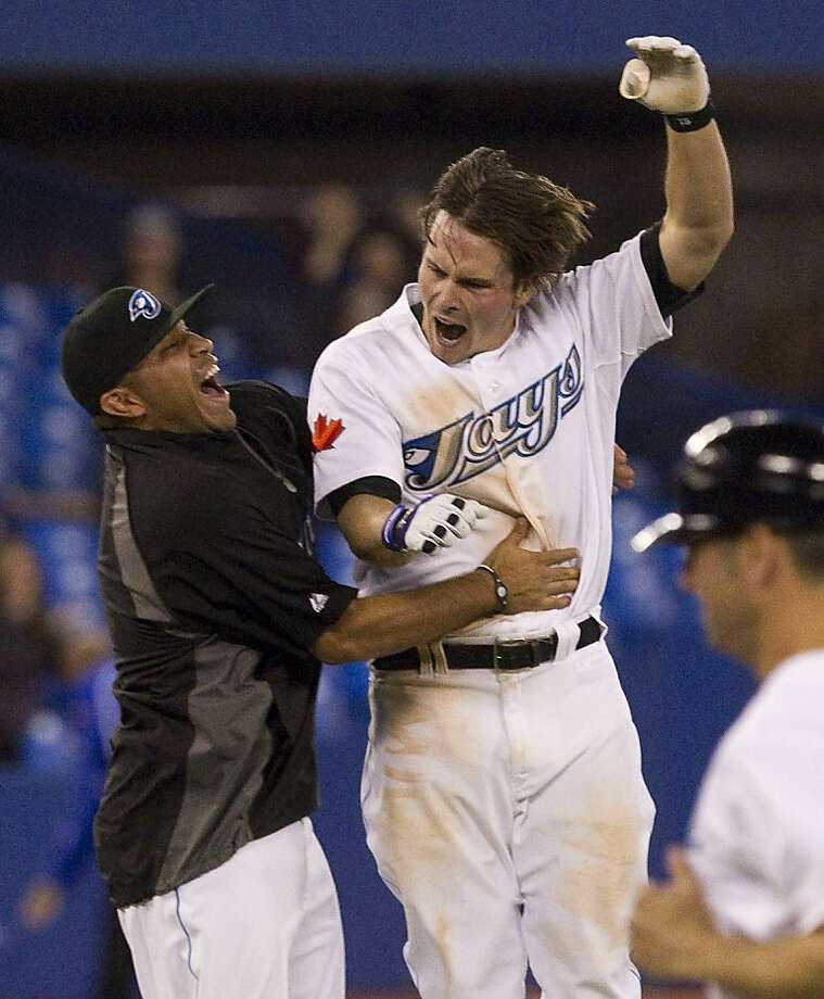 Toronto Blue Jays  Travis Snider jumps into the arms of Ricky Romero  after hitting a double to deep center to bring in Edwin Encarncion to beat New York Yankees  6-5 during the tenth  inning of  a major league baseball game in Toronto on Tuesday, April 19, 2011. Photo: Chris Young, AP