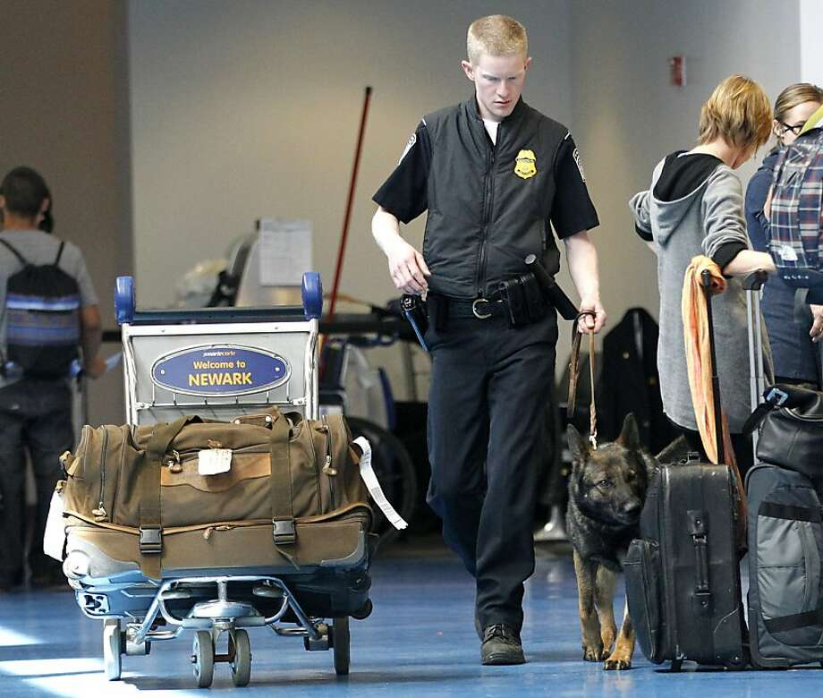 "Matt McGirr, a K-9 Enforcement officer with the Customs and Border Protection, walks with a security dog named ""Thor"" while inspecting baggage at the international terminal of Newark Liberty International Airport, Thursday, April 14, 2011 in Newark, N.J. Photo: Julio Cortez, AP"