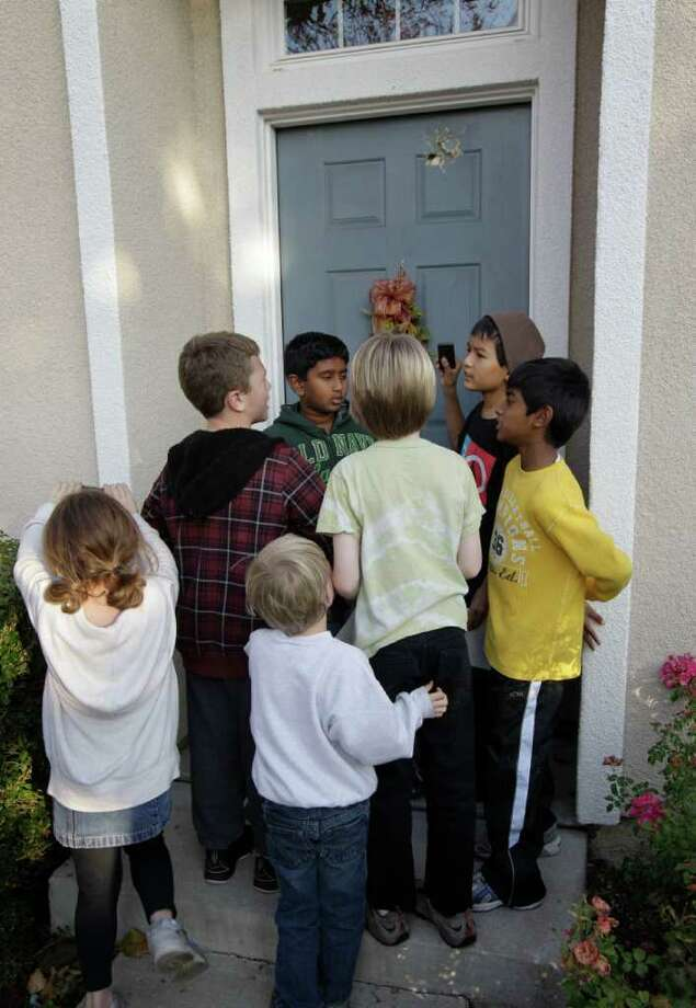 """Children gather at the front door of a Dublin, Calif. home where an errant cannonball fired during a filming of an episode of """"Mythbusters"""" entered the home Wednesday, Dec. 7, 2011. Sheriff's deputies are still measuring how, exactly, the cannonball flew from a bomb range in the rolling hills flanking a suburban San Francisco Bay area neighborhood and rocketed into the front door of a home and through its master bedroom before landing in a neighbor's parked minivan. Photo: Ben Margot"""