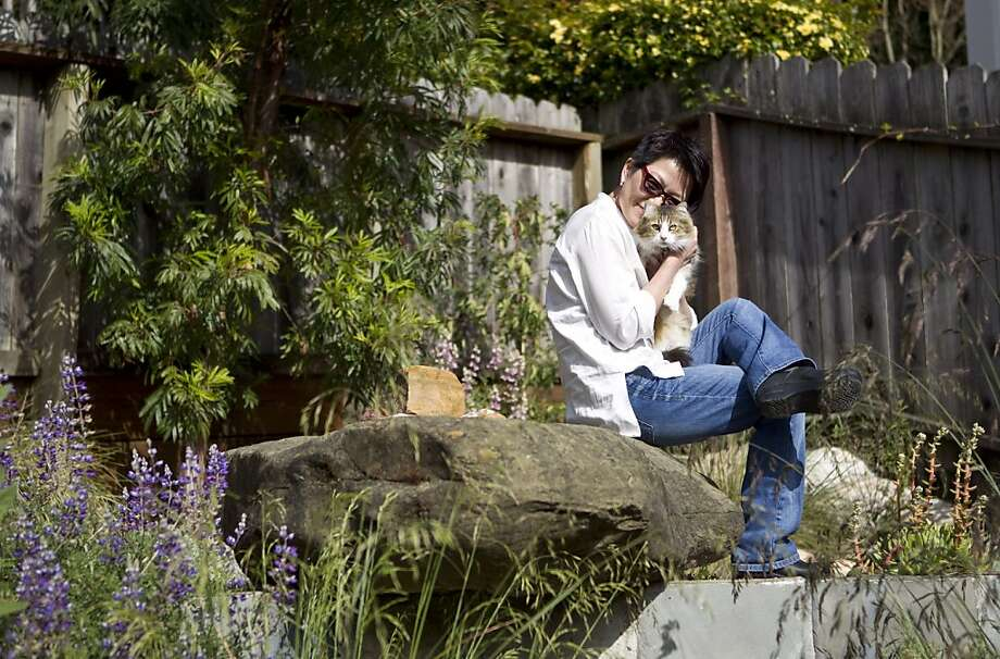 Wen Shen sits in her backyard garden with her cat Girlfriend at her home in Oakland, Calif., on Tuesday, April 12, 2011.  Shen's garden will be one of the stops on the Bringing Back the Natives Garden Tour. Photo: Laura Morton, Special To The Chronicle