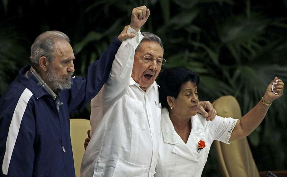 Fidel Castro, left, raises his brother's hand, Cuba's President Raul Castro, center, as they sing the international socialist anthem during the 6th Communist Party Congress in Havana, Cuba, Tuesday April 19, 2011. Raul Castro was named first secretary ofCuba's Communist Party on Tuesday, with Fidel not included in the leadership for the first time since the party's creation 46 years ago. The woman at right is Nemesia Rodriguez Montano, a woman survivor of the 1961 Bay of Pigs failed invasion by U.S.-backed Cuban exiles . Photo: Javier Galeano, AP