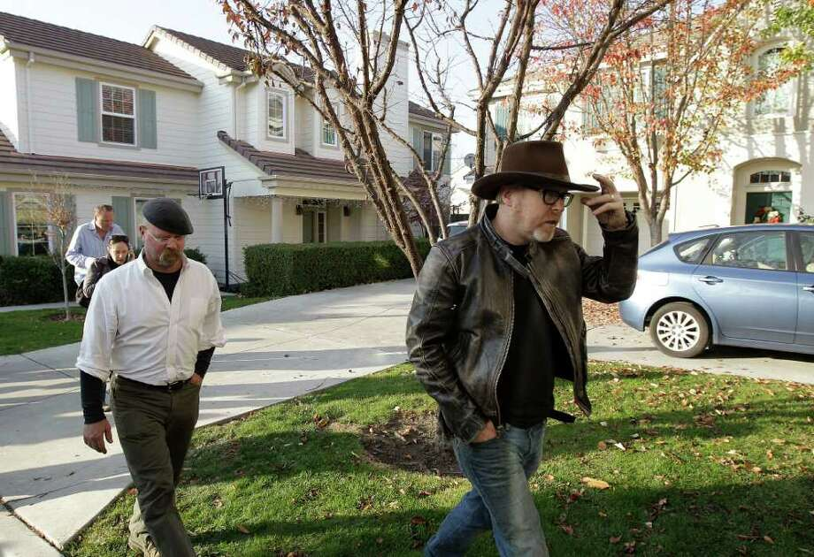 """Mythbusters"" stars Adam Savage, right, and Jamie Hyneman approach the home damaged by an errant cannonball fired during a filming of an episode of their show, Wednesday, Dec. 7, 2011 in Dublin, Calif. Sheriff's deputies are still measuring how, exactly, the cannonball flew from a bomb range in the rolling hills flanking a suburban San Francisco Bay area neighborhood and rocketed into the front door of a home and through its master bedroom before landing in a neighbor's parked minivan. Photo: Ben Margot"