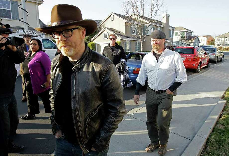"""Mythbusters"" stars Adam Savage, left, and Jamie Hyneman approach the home damaged by an errant cannonball fired during a filming of an episode of their show, Wednesday, Dec. 7, 2011 in Dublin, Calif. Sheriff's deputies are still measuring how, exactly, the cannonball flew from a bomb range in the rolling hills flanking a suburban San Francisco Bay area neighborhood and rocketed into the front door of a home and through its master bedroom before landing in a neighbor's parked minivan. Photo: Ben Margot"