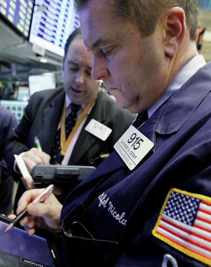 FILE - In this Nov. 7, 2011 file photo, trader Anthony Cerar, right, works on the floor of the New York Stock Exchange. World stocks rose Wednesday, Dec. 7, 2011, amid growing optimism that European leaders will approve aggressive plans by the end of the week to rescue the region from a debt crisis that has roiled financial markets for months.(AP Photo/Richard Drew, File) Photo: Richard Drew