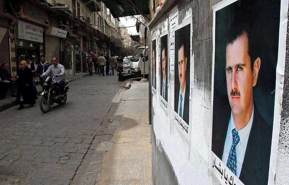 Posters of Syrian President Bashar al-Assad decorate a street as Syrians walk in the old city of Damascus on April 2, 2011. Photo: Anwar Amro, AFP/Getty Images