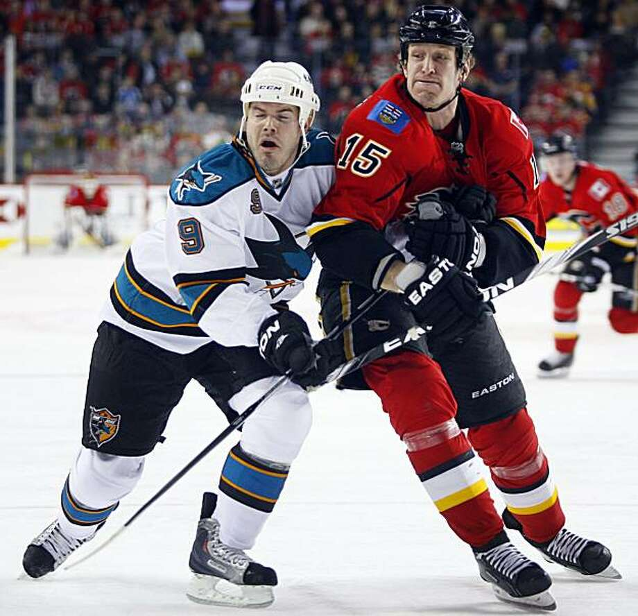 San Jose Sharks' Ian White, left, and Calgary Flames' Tim Jackman collide during first-period NHL hockey game action in Calgary, Alberta, Friday, Feb. 25, 2011. Photo: Jeff McIntosh, AP