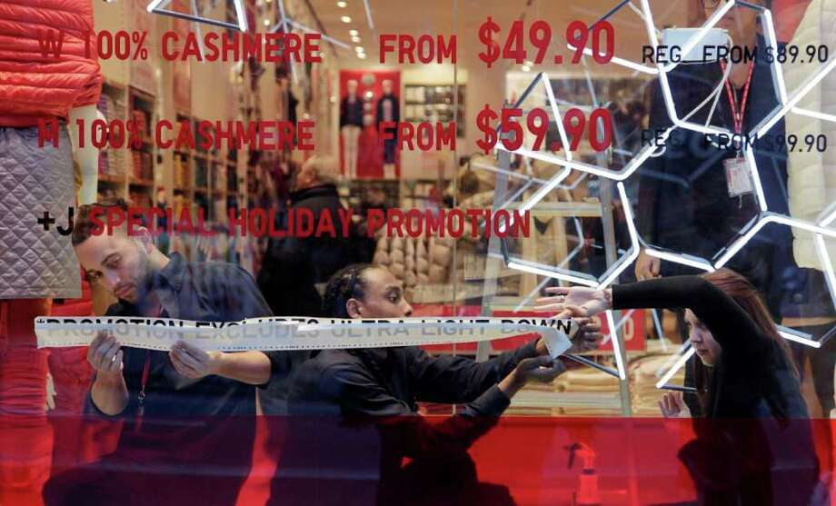 In this Dec. 1, 2011 photo, employees of Uniqlo paste promotional information in a window of the retailer's New York store. Used to be, customers would come running when stores cut prices. But Americans have become increasingly blase about bargains during this holiday season.(AP Photo/Mark Lennihan) Photo: Mark Lennihan