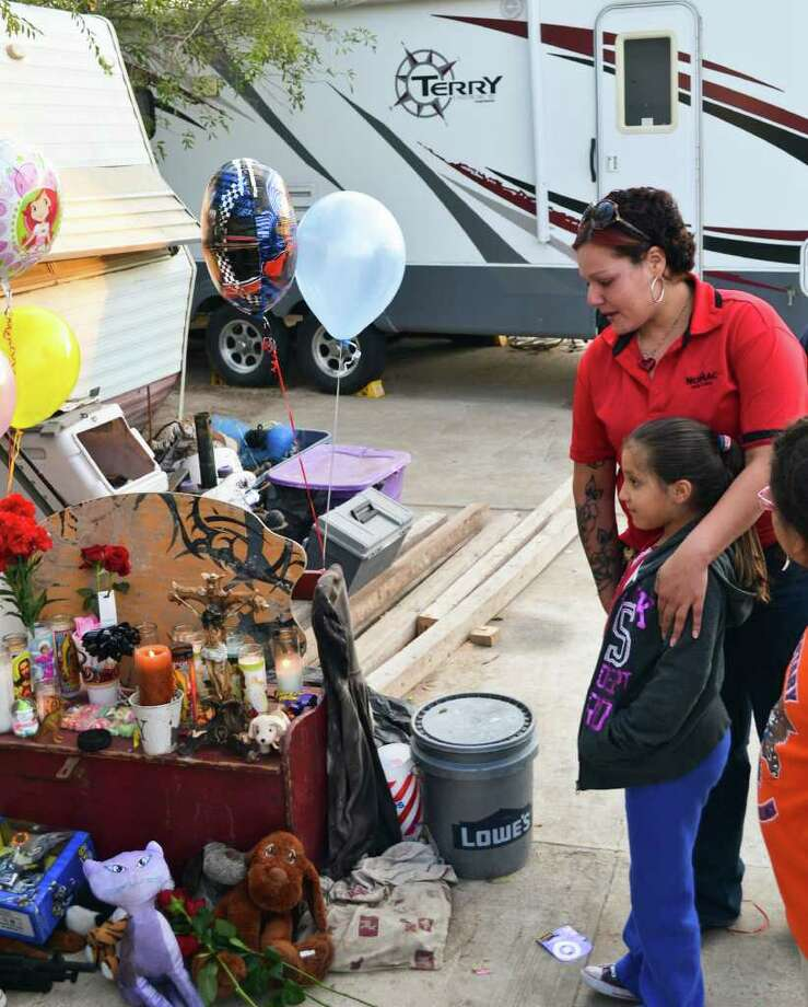 Naomi Salinas and her daughter Jannette drove across town to place flowers on the shrine for Rachelle, Timothy and Ramie Grimmer in front of the family's RV in Laredo. Photo: Jason Buch, San Antonio Express-News