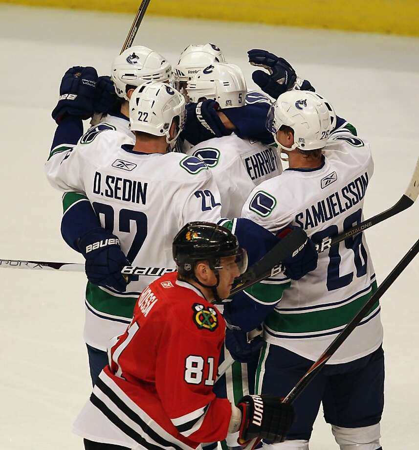 CHICAGO, IL - APRIL 17: Members of the Vancouver Canucks including Daniel Sedin #22 and Mikael Samuelsson #26 celebrate a 2nd period goal by Christian Ehrhoff #5 (center) as Marian Hossa #81 of the Chicago Blackhawks skates off of the ice in Game Three ofthe Western Conference Quarterfinals during the 2011 NHL Stanley Cup Playoffs at the United Center on April 17, 2011 in Chicago, Illinois. Photo: Jonathan Daniel, Getty Images
