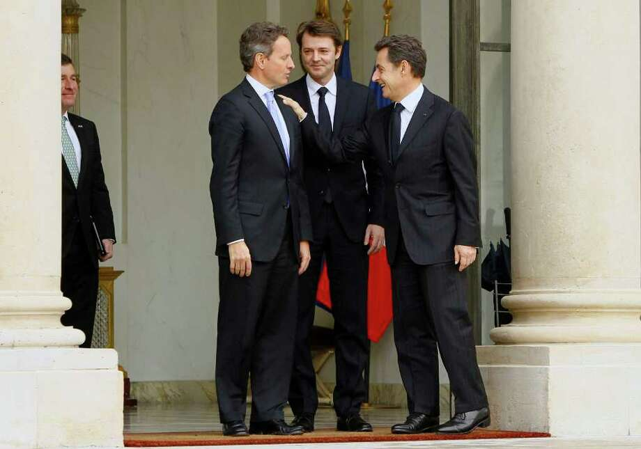 France's President Nicolas Sarkozy, right, accompanies U.S. Treasury Secretary Timothy Geithner , left, as Finance Minister Francois Baroin, center, looks on after their meeting at the Elysee Palace in Paris, Wednesday, Dec. 7, 2011. U.S. Treasury Secretary Timothy Geithner is touring across Europe with a stark message, for the continent's leaders must act quickly and convincingly to defuse a debt crisis that is threatening the global economy. His visit this week comes on the eve of a summit of European leaders Friday that could yield a plan for resolving the crisis. (AP Photo/Francois Mori) Photo: Francois Mori / AP