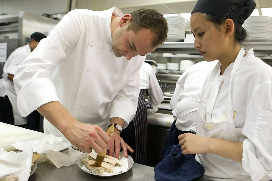 Chef Daniel Humm brushes black truffel poached chicken breasts, as cook Lucy Tran, right, assists, before the chicken is plated at the Campton Place Restaurant in the Taj Campton Place Hotel in San Francisco Saturday night, November 19, 2011. Chef Humm, who used to be the executive chef at Campton Place restaurant has prepared the prix fixe meal in celebration of his new cookbook titled after his New York City restaurant, Eleven Madison Park. The cookbook is co-authored with his business partner and Eleven Madison Prak restaurant co-owner, Will Guidara. Photo: Erin Lubin, Special To The Chronicle