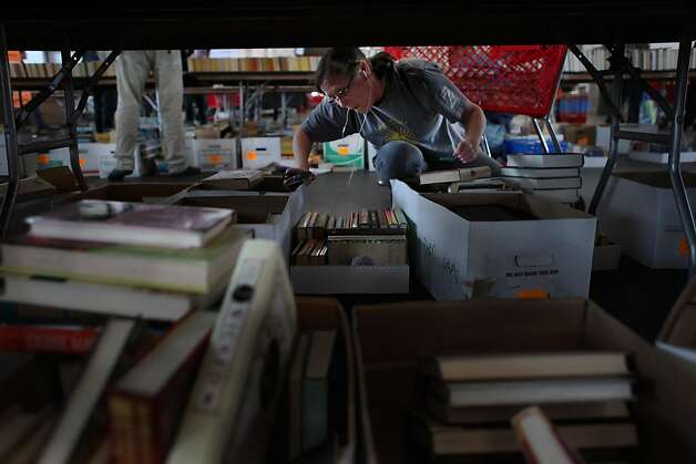 Prescilla Molitor of San Diego looks through boxes of books and scans them under a table at the Friends of the San Francisco Public LibraryÍs special 50th Anniversary book sale at Fort Mason in San Francisco, Calif., Thursday, April 21, 2011. Molitor was first in line at Thursday's sale and says she will be attending every day of the sale. Photo: Lea Suzuki, The Chronicle