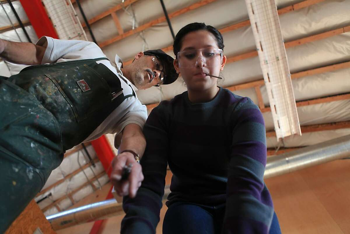 Gus Amador (l to r), carpentry teacher, gives John O'Connell High School junior, Lucerito Martinez, 16, tips while a group of advanced carpentry students work together to rough frame a stage being built in the new industrial arts building at John O'Connell High School on Wednesday, December 7, 2011 in San Francisco, Calif. The stage was being built for a ceremony for the new building to be held the next day.