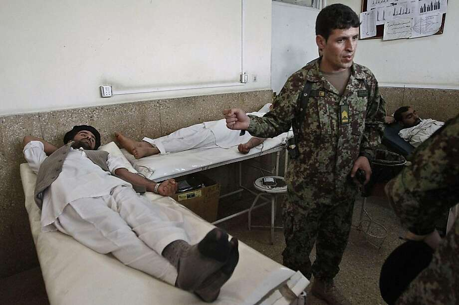 Wounded Afghans lie on beds at the main hospital in Jalalabad on April 16, 2011, after they were injured in an attack. A Taliban suicide bomber wearing an army uniform killed five foreign troops and four Afghan soldiers in a brazen attack at the Afghan army's eastern headquarters. It was the deadliest single incident this year against foreign forces in war-torn Afghanistan and comes amid a wave of suicide attacks on security targets, three months before foreign forces start a limited pullback. Photo: Str, AFP/Getty Images