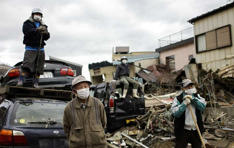 Japanese men watch a crane dismantling a house in the area devastated by the March 11 earthquake and tsunami in the port town of Kesennuma, Iwate Prefecture, Japan, Wednesday, April 20, 2011. Photo: Sergey Ponomarev, AP