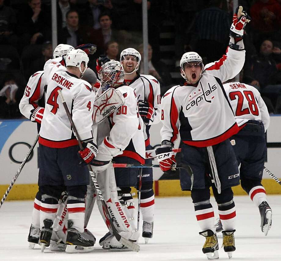 Teammates watch as Washington Capitals left wing Alex Ovechkin (8) celebrates after the Capitals defeated the New York Rangers 4-3 in the second overtime of Game 4 of an NHL hockey Stanley Cup first-round playoff series, at Madison Square Garden in New York on Wednesday, April 20, 2011. Photo: Kathy Willens, AP