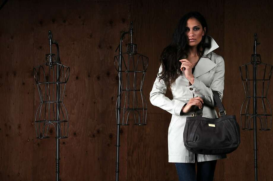 "Hlaska's new women's accessories and apparel line offers this Miner's Wife trenchcoast ($395) with a leather ""Artifact"" handbag in charcoal ($495). Photo: Hlaska"
